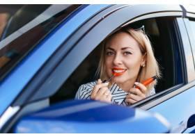 年轻的高加索女子涂抹口红看着车镜中的倒_10284872