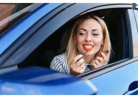 年轻的高加索女子涂抹口红看着车镜中的倒_10284876