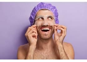 开朗的年轻人戴着保湿面膜戴着浴帽裸体_12494382