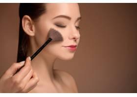 拿着化妆刷的美女完美的皮肤化妆_9368076