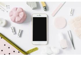 智能手机的俯视视图白色表面上环绕着各种_3631473
