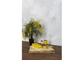 木板上的黄色含羞草花瓶上面有香皂和精油_4173698