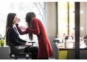模特在专业化妆过程中坐在高脚椅上_9187562