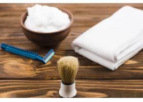 泡沫碗前有经典剃须刷木桌上有折叠的白色_4183296