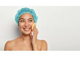 漂亮的年轻女子用海绵洗脸抚摸脸颊戴着_12495202