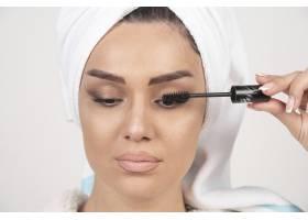 用白毛巾裹着的女人涂睫毛膏的肖像_11778964