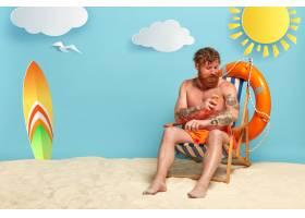 留着胡须的红头发涂着防晒霜在海滩上摆姿_12607728