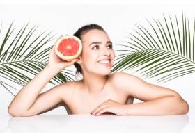 皮肤完美的年轻女子手持柑橘类水果周围环_8990764