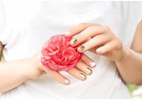 美丽的女性手完美的金色和粉色指甲设计_9129490