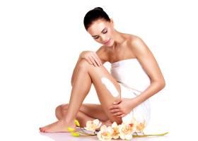 美丽的年轻女子手持鲜花正在使用这种面霜_11916570