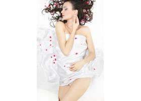 幸福美丽的年轻黑发女孩盖着床单白色上_7090386