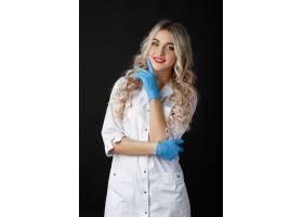 微笑的金发女医生戴着蓝色手套在演播室摆姿_2437635