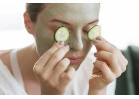 戴面膜的妇女把黄瓜片放在上面_8046365