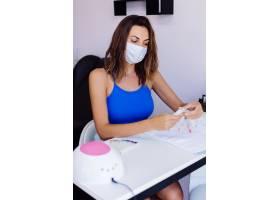 美甲美容院里戴着防护医用口罩的年轻美女_11476301