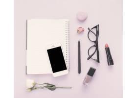 桌上有智能手机鲜花和化妆品的笔记本_3866175