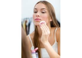 漂亮的年轻女子在家里的镜子旁卸妆_1624872