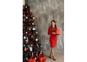 身穿红色连衣裙的美女在富丽堂皇的圣诞树前_3987021