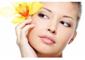 迷人的亚洲女性面孔白色隔开耳朵上的花朵_10626794