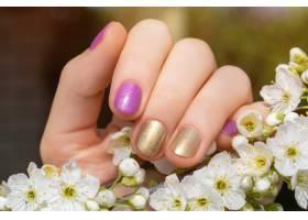 金色和紫色指甲设计的女性手握着盛开的樱花_9129831