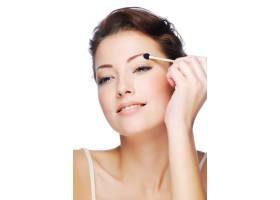 用化妆品涂抹器涂抹眼影的年轻高加索女子的_10878127