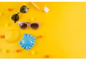 俯瞰太阳镜防晒乳液瓶黄色背景上的扇贝_4538124