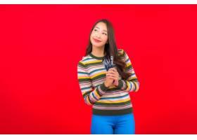 在红墙上用化妆刷和化妆品为美丽的亚洲年轻_12045208