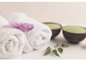 卷起毛巾上的兰花白色背景上有温泉盐_2690903