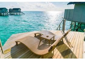 马尔代夫海滨别墅日落时间木地板上的两张躺_1129667