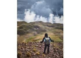 站在山上欣赏多云天空的景色的人_9654459
