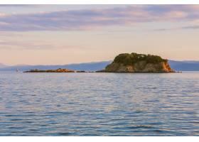 粉色天空下平静的海面上悬崖的宽阔风景_8048624