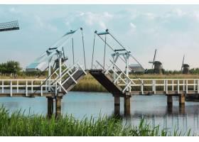 美丽的传统荷兰风车靠近带吊桥的水道_9480230