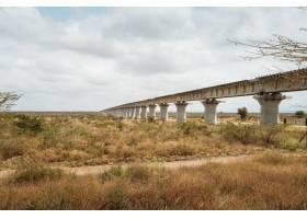 肯尼亚内罗毕拍摄的多云天空下沙漠上的长桥_8989943