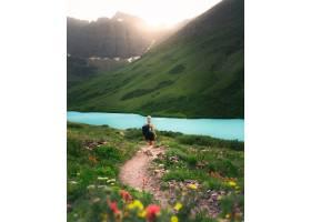 背着背包的女徒步旅行者走在一条狭窄的小路_7552359