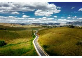 被绿树成荫的小山包围的道路多云的天空下_10186750