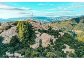 覆盖着绿树成荫的岩石悬崖顶部有一个十字_7926276