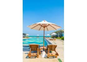 酒店和度假村游泳池周围有漂亮的伞和椅子_3661519