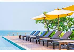 酒店度假村室外游泳池周围漂亮的空椅和雨伞_6899604