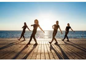 日出时分在海边跳尊巴舞的风趣女子的剪影_7591371