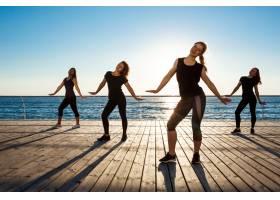 日出时分在海边跳尊巴舞的风趣女子的剪影_7591377