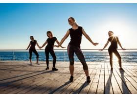 日出时分在海边跳尊巴舞的风趣女子的剪影_7591378