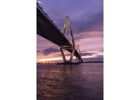 日落时分在多云的天空下海上一座桥的垂_9991277