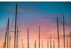 日落时分拍摄的帆船桅杆剪影的美丽镜头_7814421