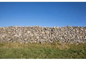 晴朗天空下绿色田野中的石墙的美丽镜头_10835481