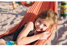 海滩上穿着黑色泳衣的可爱小女孩_12965072