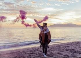 男子将手持粉色烟雾弹的女子抱回海边_3641347