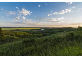 在晴朗的蓝天和粉色的天空下白云笼罩着草_7841789