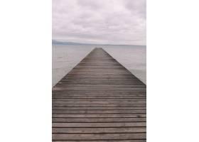 在美丽多云的天空下木制码头在平静的海洋_10304035