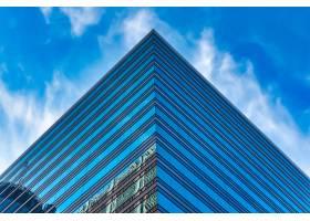 在蓝色多云的天空下低角拍摄一座高大的玻璃_10499866