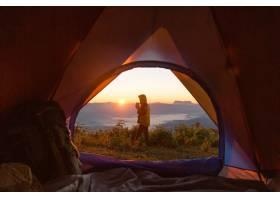 徒步旅行者站在露营前橙色的帐篷和背包在_4351625