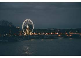 巴黎夜里摩天轮被河流和多云天空下的建筑_9852528